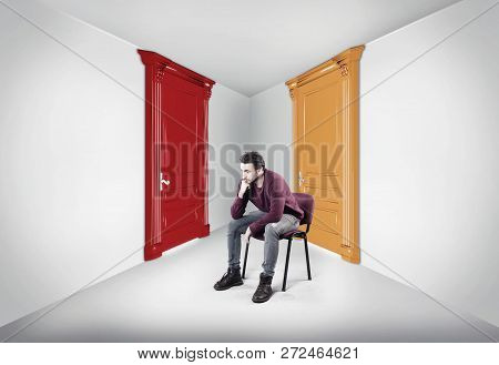 Thoughtful Man Between Two Doors. The Concept Of Choosing The Right Path.