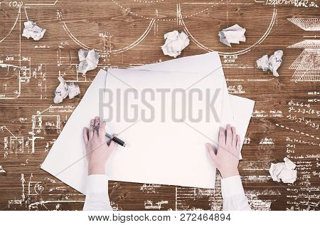 Top View Of Hands On Blank Paper On A Wooden Table Drawn With A Sketch And Plan.