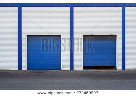 White Industrial Warehouse With Blue Door For Trucks