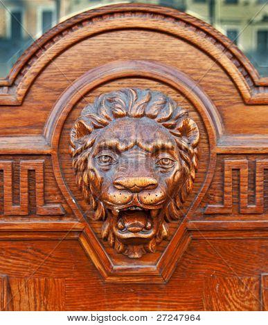 Big wooden head of lion on the front door