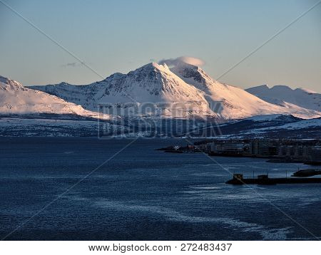 Troms Region. Rocky Coast Of Fjord In Winter With Snow And Ice. Snowy Mountains And Fishing Village