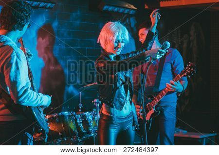 Band during gig making rock music on stage together