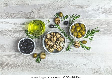 Set Of Black And Green Olives, Quail Eggs On Plates, Olive Oil And Rosemary, On A Light Gray Wooden