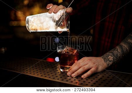 Bartender Pouring A Tasty Godfather Cocktail From The Measuring Cup Through The Strainer To A Glass