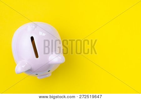 Top View Of Pink Piggy Bank On Yellow Background With Copy Space As Debt Or Financial Problem Soluti