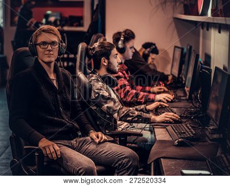 A Young Smart Gamer Wearing A Sweater And Glasses Sitting On A Gamer Chair And Looking At A Camera I