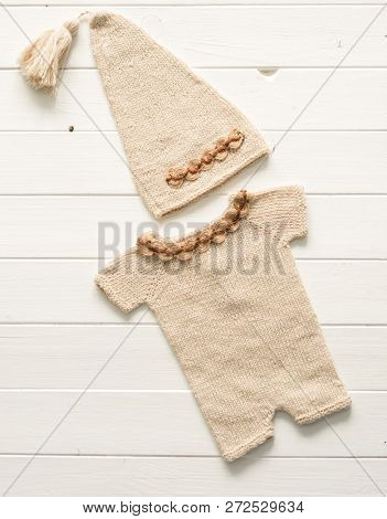 Colorful small knitted clothes for babies composed on the white table