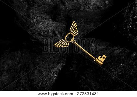 Golden Antique Key With Wings On Dark Black Background