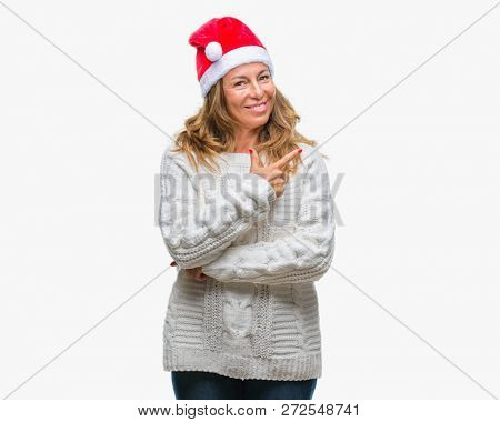 Middle age senior hispanic woman wearing christmas hat over isolated background cheerful with a smile of face pointing with hand and finger up to the side with happy and natural expression on face
