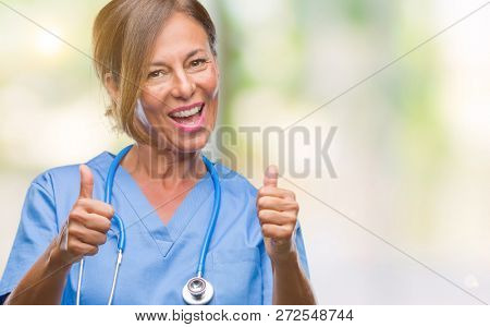Middle age senior nurse doctor woman over isolated background approving doing positive gesture with hand, thumbs up smiling and happy for success. Looking at the camera, winner gesture.