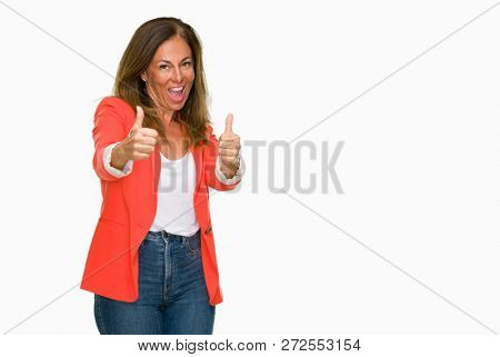 Beautiful middle age business adult woman over isolated background approving doing positive gesture with hand, thumbs up smiling and happy for success. Looking at the camera, winner gesture.