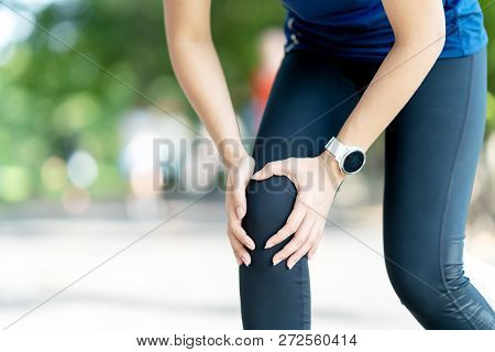 Young Asian Woman Holding Knee Pain In Running Public Nature Park In The Morning. Joint Injury In At