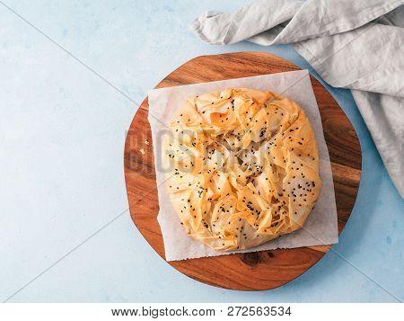Greek Pie Spanakopita On White Baking Paper Over Blue Background. Vegetarian Or Vegan Spanakopita Sp
