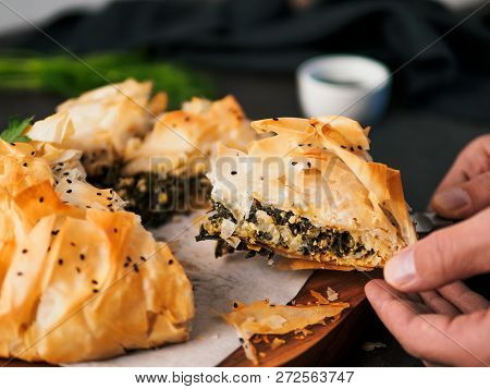 Slice Of Greek Pie Spanakopita In Hand. Ideas And Recipes For Vegetarian Or Vegan Spanakopita Spinac