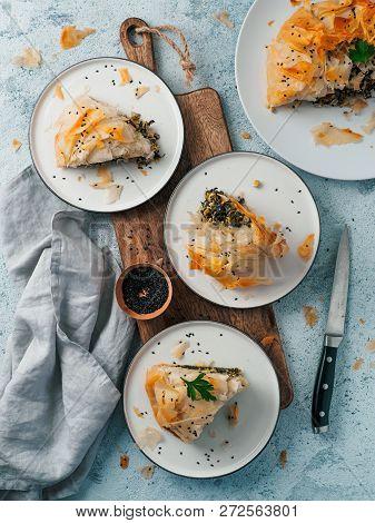 Greek Pie Spanakopita On Gray Background. Ideas And Recipes For Vegetarian Or Vegan Spanakopita Spin