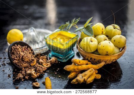 Close Up Of Indian Gooseberry Or Amla With Turmeric And Lemon Juice On Wooden Surface In A Glass Bow