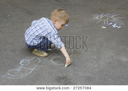 child drawing on asphalt car