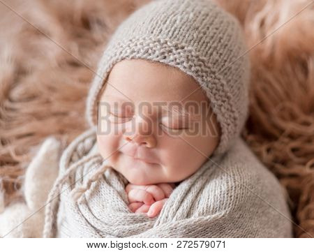 Little cute baby weared in gray knitted beanie and covered with gray knitted blanket sweetly sleeping with bunny nearby on the soft light brown bedcover