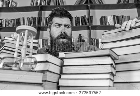 Teacher Or Student With Beard Sits At Table With Books, Defocused. Bibliophile Concept. Man On Confu