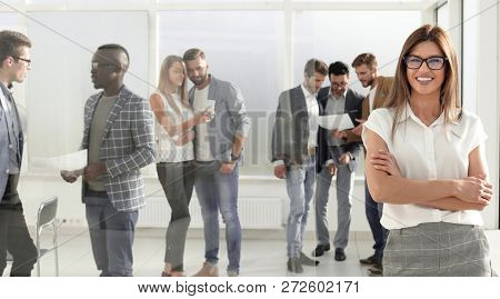 business woman and a group of employees standing in the office