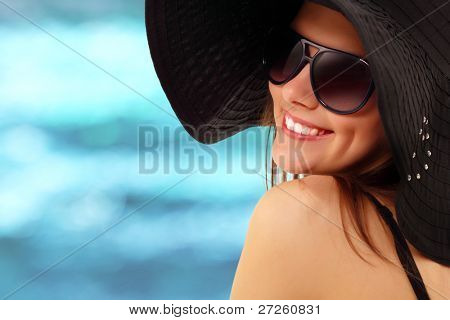 summer teen girl cheerful in panama and  sunglasses enjoying over water nature background