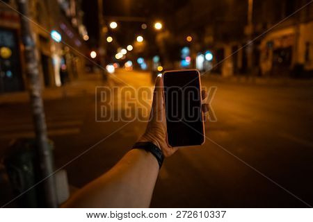 A Mans Hand Holding A Smartphone With A Black Screen.
