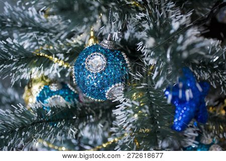 brilliant, in spangles, a blue ball hung on a branch of an artificial Christmas tree alongside other silver and golden toys poster