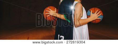 Two Boys Basketball Team Players Holding Basketballs On The Wooden Court. Basketball Training For Ki
