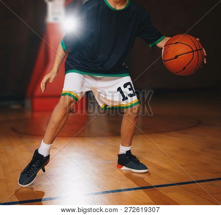 Kids Basketball Training. Young Basketball Player Dribble The Ball On The Wooden Court. Basketball T