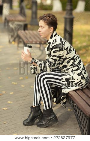 Short Haired Brunette Girl In Black And White Clothes With Cup Sitting In Park Outdoor