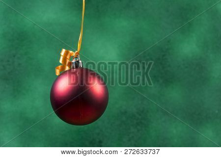 Red Christmas Ball Hanging With Orange Ribbon On Green Background.