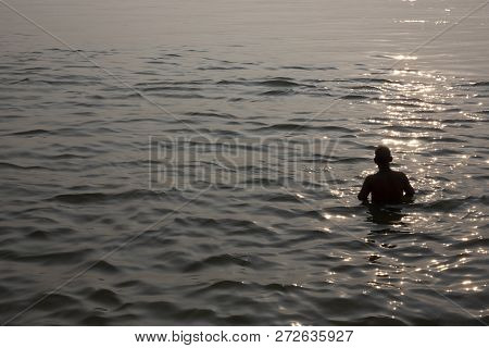 Silhouette Of A Man Taking Bath In Ganges River During Sunset, India
