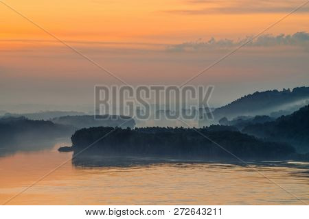 Morning mystic haze above broad valley of river. Gold glow from dawn in sky. Riverbank with forest under fog. Sunlight reflected in water at sunrise. Colorful atmospheric landscape of majestic nature. poster