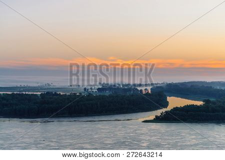 Early blue sky reflected in river water. Riverbank with forest under predawn sky. Orange stripe in picturesque sky. Fog hid trees on island. Colorful morning atmospheric landscape of majestic nature. poster