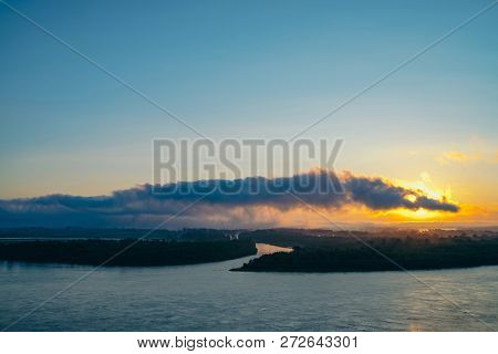 Riverbank with forest and fog. Orange glow from picturesque dawn reflected in river. Sun shines through cloud of snake or crocodile shape. Mystical morning atmospheric landscape of majestic nature. poster