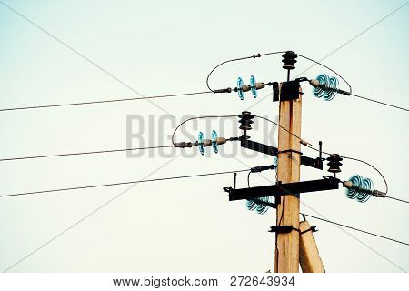 Power Lines On Background Of Blue Sky Close-up. Electric Hub On Pole. Electricity Equipment With Cop