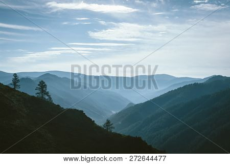 Morning Mist Above Valley Between Silhouettes Of Mountain Slopes On Horizon In Backlighting. Blue Gl