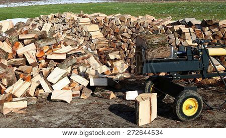 Yellow and black log splitter ready to split horizontally with blocks, heap and woodpile poster