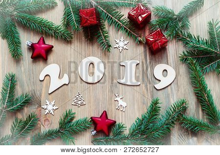 New Year 2019 background with 2019 figures, Christmas toys, green fir tree branches and snowflakes. New Year 2019 festive seasonal still life in retro tones