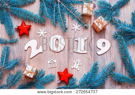 New Year 2019 background -2019 figures, Christmas toys, bright blue fir tree branches and snowflakes. New Year 2019 festive seasonal still life