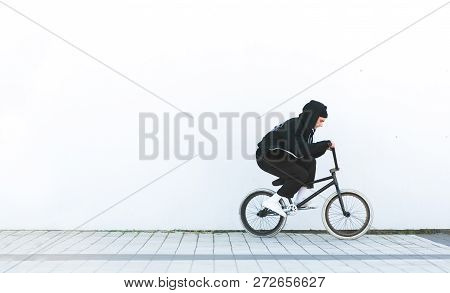 Bmx Rider In Casual Clothing Rides A Bicycle On The Background Of A White Wall. Bmx Concept. Street