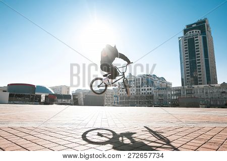 Street Portrait Of A Bmx Rider In A Jump On The Street In The Background Of The City Landscape And T