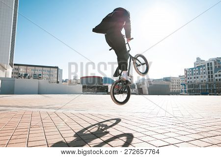 Bmx Rider Makes A Trick In The Jump On The Street In The Background Of The City Landscape And The Su