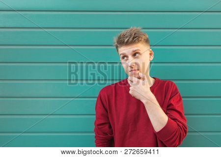 Beautiful Young Student Standing On A Turquoise Background And Looking At Copyspace With A Thoughtfu