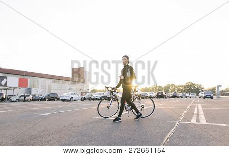Young Cyclist Walks With A White Bicycle In The Parking Lot Against The Background Of The Sunset. Cy