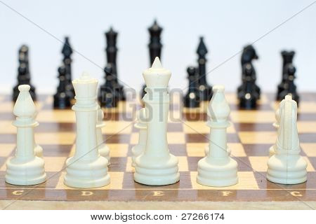 The image of the beginning of chess game. Focus is under the white queen