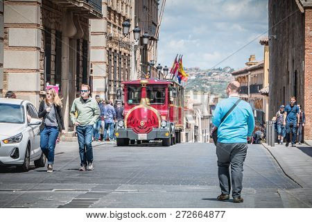 Toledo, Spain - April 28, 2018: Tourist Strolling In A Street Of The Historic District Next To A Sma