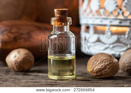 A Bottle Of Nutmeg Essential Oil With Dried Nutmeg