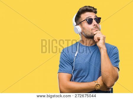 Young handsome man wearing headphones listening to music over isolated background with hand on chin thinking about question, pensive expression. Smiling with thoughtful face. Doubt concept.