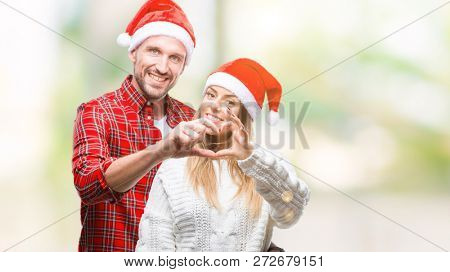 Young couple in love wearing christmas hat over isolated background smiling in love showing heart symbol and shape with hands. Romantic concept.